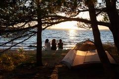 三个旅游女孩背面图坐在享受美好的日落的帐篷前面的湖岸 免版税库存图片