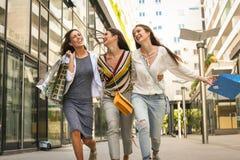 三个时兴的在购物以后的女孩走的愉快的城市 免版税库存图片