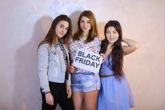 三个时髦的女性朋友摆在与标志和要求嘘 免版税图库摄影