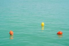 三个明亮的黄色和橙色标志漂浮漂浮在蓝色tur 图库摄影