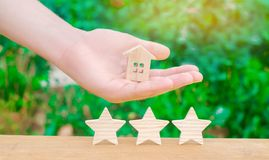 三个星和拿着房子的手 卖和买家的概念 物产的估价 优质和可靠 库存图片