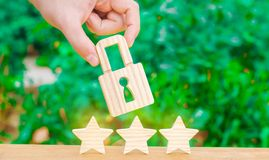 三个星和拿着锁的手 优质和保护的概念 结果和成就的实变 免版税图库摄影
