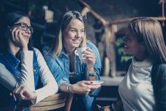 三个最佳的女朋友谈话在咖啡馆 免版税库存照片
