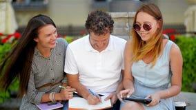 三个朋友画象为检查做准备使用黑片剂 两个女孩和一项男孩研究户外坐 股票视频