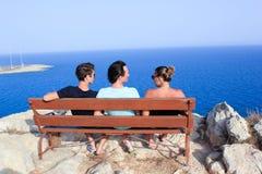 三个朋友罕见的焦点坐长凳在海边meditarian海在塞浦路斯,7月东部 库存照片