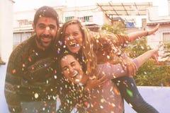 三个朋友非常愉快在屋顶党和投掷的五彩纸屑 免版税库存图片