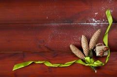 三个杉木锥体栓与绿色丝带平伏在木蟒蛇 库存图片