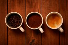 三个杯子浓咖啡,新近地碾碎的咖啡和咖啡豆在一张木桌上 库存照片