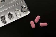 三个桃红色药片和空的天线罩包装 库存照片