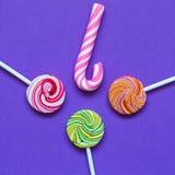 三个棒棒糖和桃红色焦糖螺旋棍子 免版税库存照片