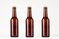 三个棕色longneck啤酒瓶330ml嘲笑 在白色木桌上的模板 图库摄影