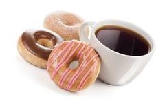 三个油炸圈饼和一个大杯子无奶咖啡或茶 库存照片