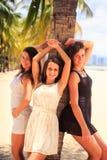 三个深色的亭亭玉立的女孩在海滩的棕榈倾斜 免版税库存图片
