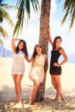 三个深色的亭亭玉立的女孩在海滩赤足站立 库存照片