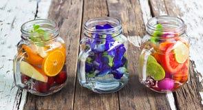 三个混合果子和草本杯子可口刷新的饮料在木头 免版税库存照片
