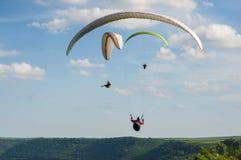 三个滑翔伞飞行在绿色领域在Dnister河附近在乌克兰 库存照片