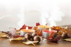 三个灼烧的蜡烛、五颜六色的北赤栎和琥珀色的项链秋叶和橡子在木板 库存图片