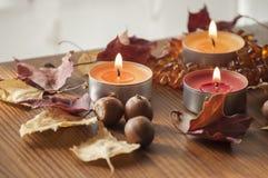 三个灼烧的蜡烛、五颜六色的北赤栎和琥珀色的项链秋叶和橡子特写镜头在木板 免版税图库摄影