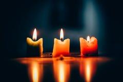 三个灼烧的蜡烛包围有深绿背景 免版税库存照片