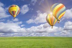 三个热空气气球,太阳火光,在绿色领域上的蓝天 库存图片