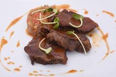 三个片断烹调烤了水多的肉,焦糖 用菜炖煮的食物 库存照片