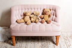 三个玩具熊坐桃红色沙发 图库摄影