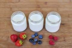三个玻璃瓶子用莓果-接近的酸奶和变异 免版税库存图片