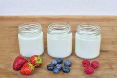 三个玻璃瓶子用莓果-接近的酸奶和变异 图库摄影