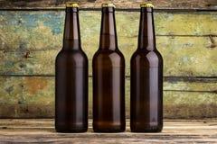 三个瓶反对木背景的啤酒 库存图片