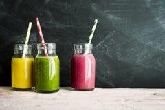 三个瓶子与秸杆的果子五颜六色的饮料 库存照片