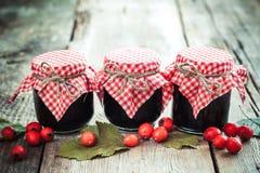 三个瓶子在桌上的果酱和山楂树莓果 免版税库存图片