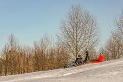 三个男孩下降在雪撬的山 库存图片