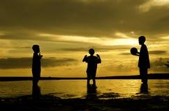 三个男孩戏剧在日落日出期间的海滩球 沙子和反射在水 库存图片