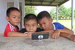 三个男孩观看兴趣在电话 免版税库存照片