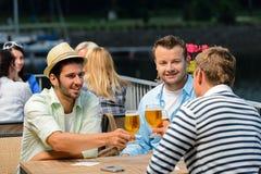 喝啤酒室外大阳台的三个男性朋友 库存照片