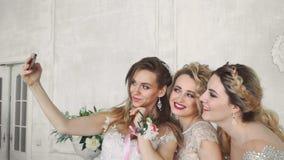 三个白肤金发的女孩做在白色墙壁背景的selfie在慢动作 影视素材