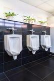 三个白色尿壶在人卫生间里 免版税库存照片