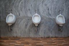 三个白色尿壶特写镜头在人` s白色卫生间设计的  图库摄影