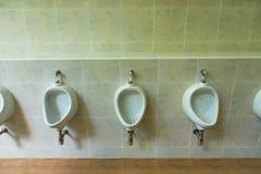 三个白色尿壶特写镜头在men& x27的; s白色卫生间设计  免版税库存照片