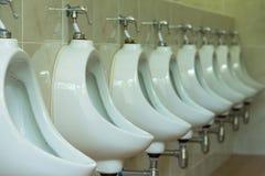 三个白色尿壶特写镜头在men& x27的; s白色卫生间设计  库存图片