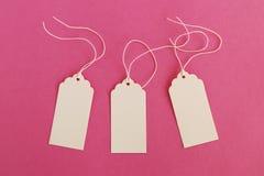 三个白色白纸价牌或标号组在桃红色背景 免版税库存图片