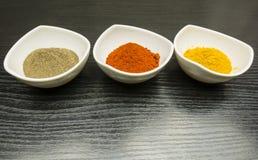 三个白色碗用香料-黑胡椒、辣椒粉和咖喱 免版税库存照片