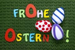 三个的复活节彩蛋和说五颜六色的信件复活节快乐用在一件绿色纺织品的德语 图库摄影