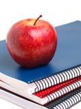 三个笔记本和红色苹果在垂直的构成 库存图片