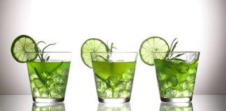 三个绿色鸡尾酒用站立在玻璃的柠檬和迷迭香在演播室,灰色背景 免版税库存照片