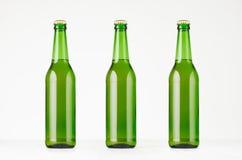 三个绿色longneck啤酒瓶500ml,嘲笑  库存照片