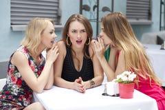 三个美丽的坐在桌上我的女朋友说闲话的妇女 免版税库存图片