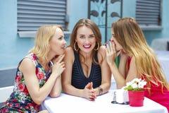三个美丽的坐在桌上我的女朋友说闲话的妇女 免版税库存照片