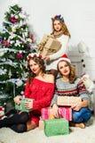 三个美丽的女孩公司在圣诞树附近的 免版税库存照片