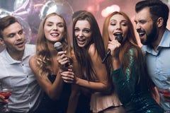 三个美丽的女孩在卡拉OK演唱俱乐部唱歌 在他们后是等待他们的轮的人 免版税库存照片